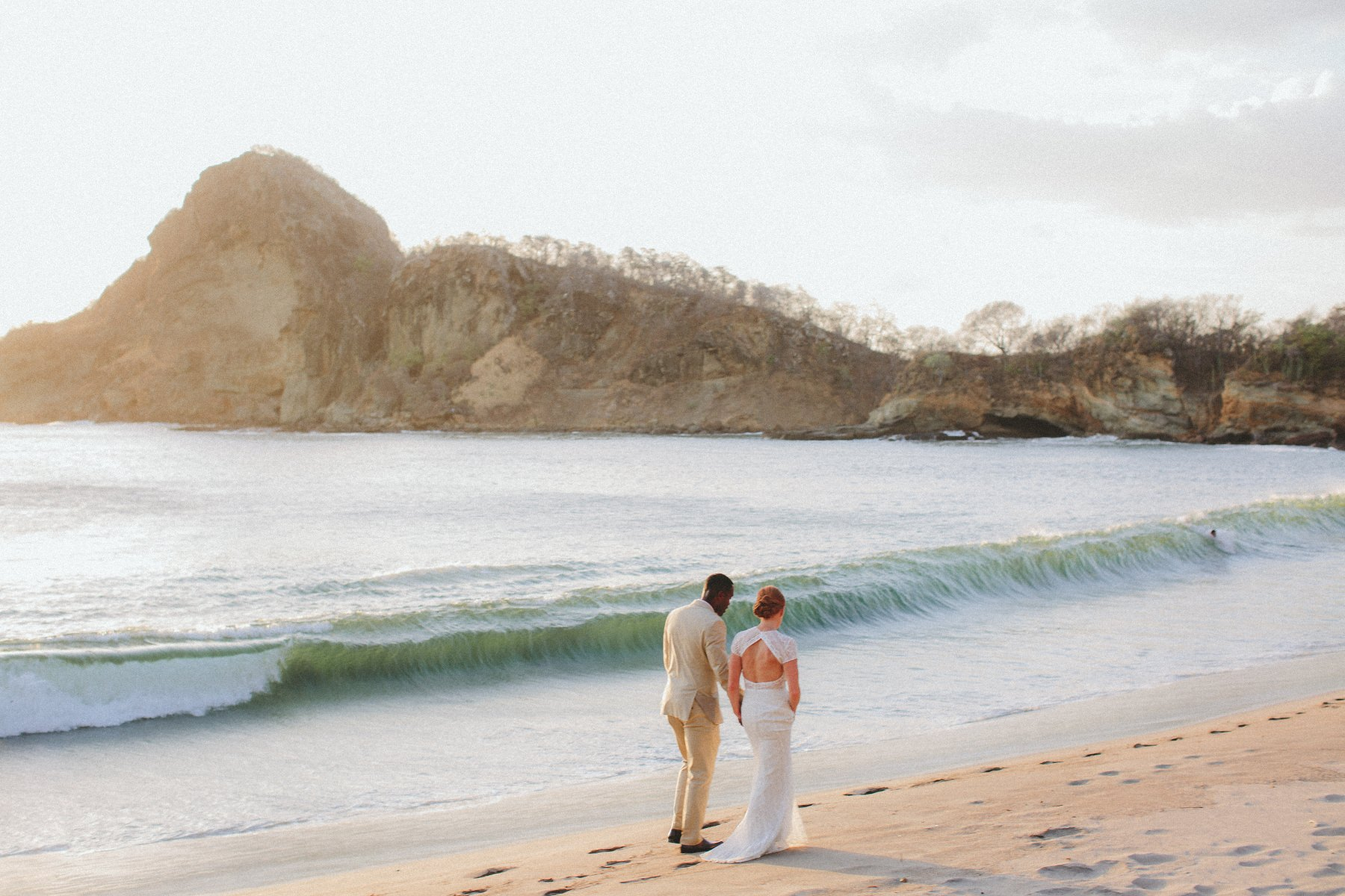 Bride and groom walking at the beach after their wedding in Nicaragua. Blue ocean and dramatic rock formations are creating a backdrop
